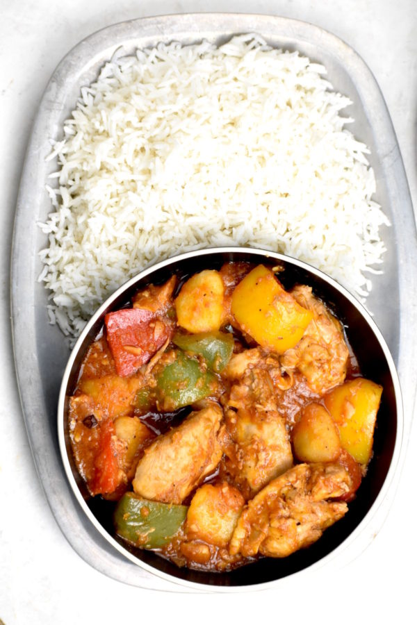 Bowlful of chicken asado on a platter full of rice.