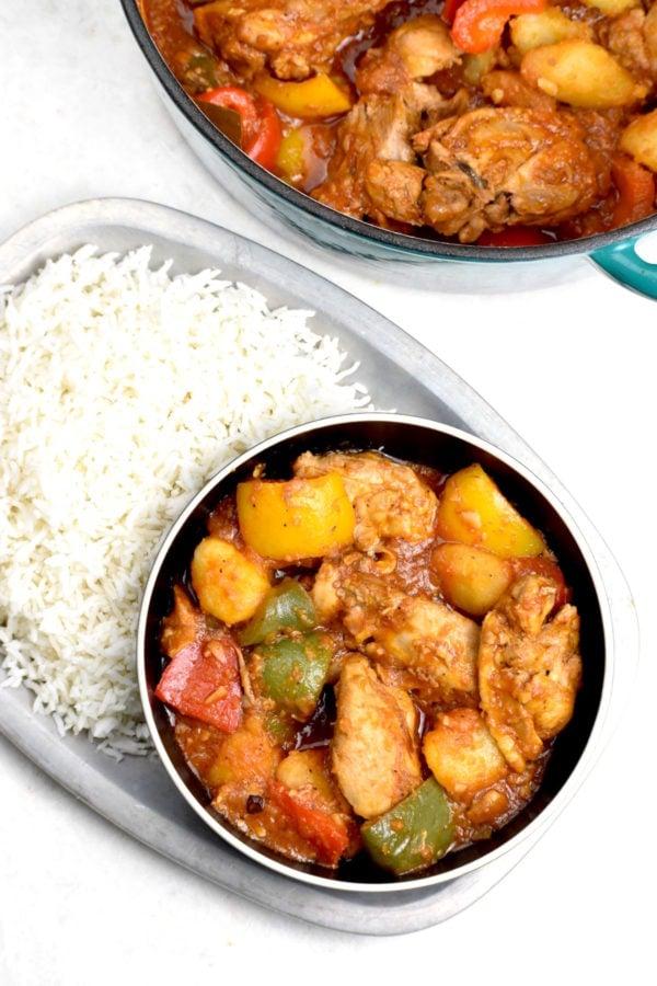 Big serving of chicken asado in a black bowl.