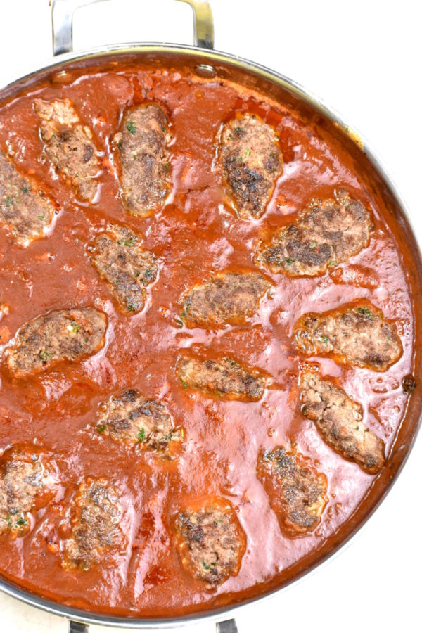 Meatballs added in to the tomato sauce in a skillet.