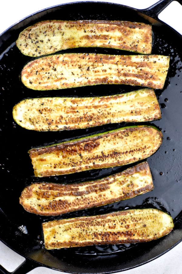 Cooked zucchini halves in a cast iron skillet.