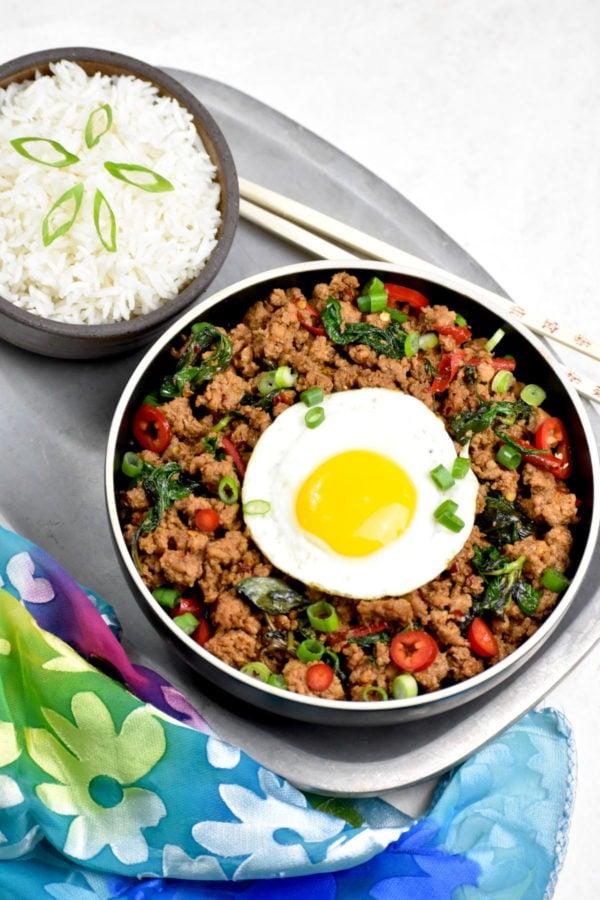 The bowl of pad krapow gai atop a metal platter.