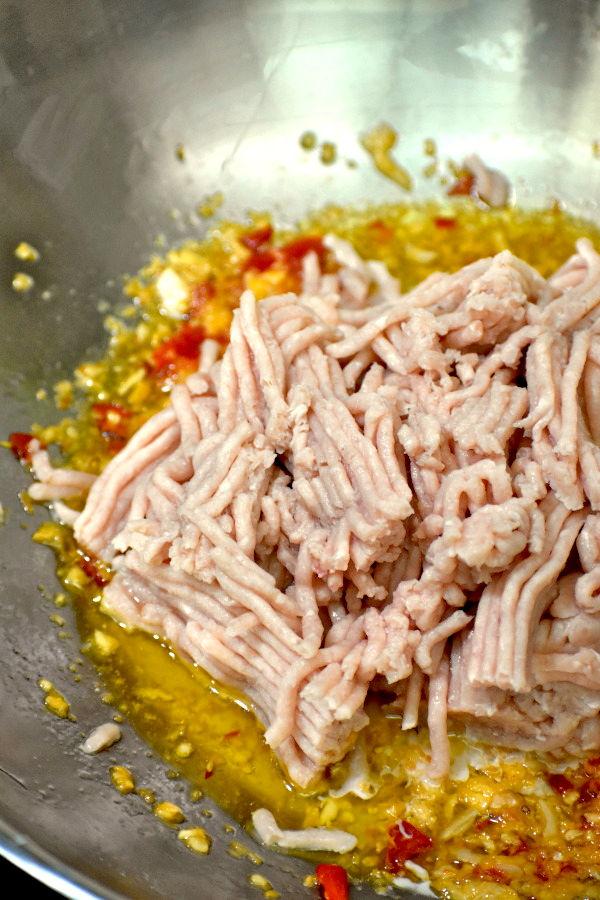 Raw ground chicken added to the wok.