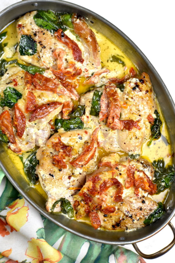 Tuscan chicken in an oval shaped metal bowl.