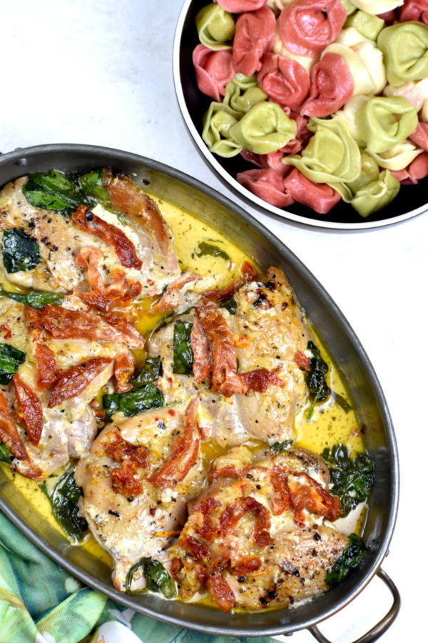 The metal bowl of Tuscan chicken next to a bowl of tri colored tortellini.