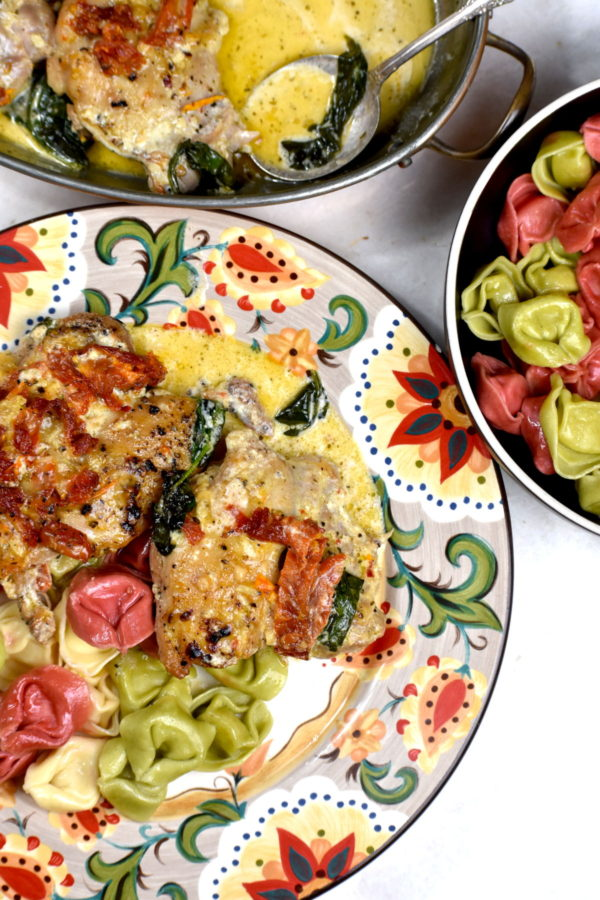 Serving of Tuscan chicken with multi colored tortellini atop the Gypsy Plate.