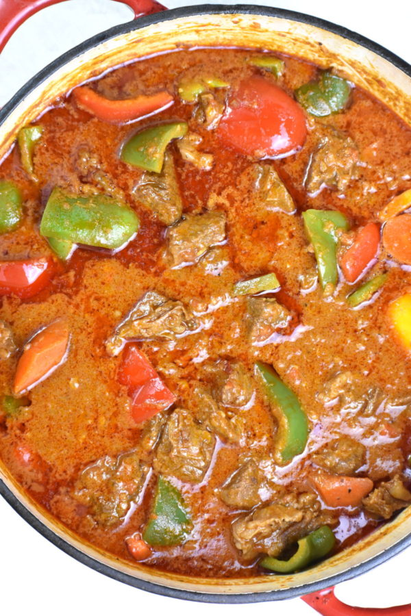 Round dutch oven full of peanut stew with beef, carrots and bell peppers.