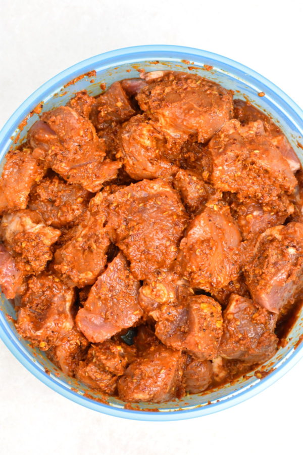 Large chunks of pork marinating in a glass bowl.