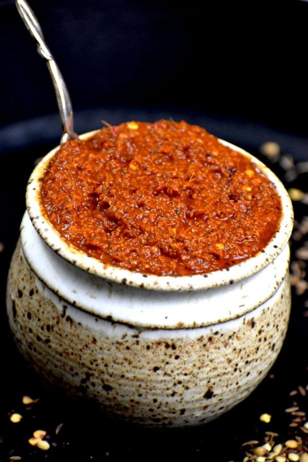 Rustic bowl full of bright red vindaloo paste.