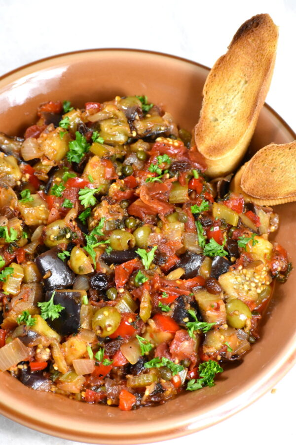 Caponata in a brown bow with two crispy slices of baguette bread.