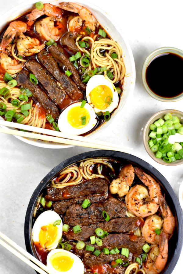 Two bowls, one white and one black, full of yakamein. This Creole soup consists of spaghetti noodles, beef, shrimp and eggs in a flavorful broth.