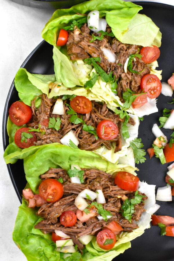 Three lettuce leaves filled with barbacoa beef and garnished with tomatoes and cilantro.