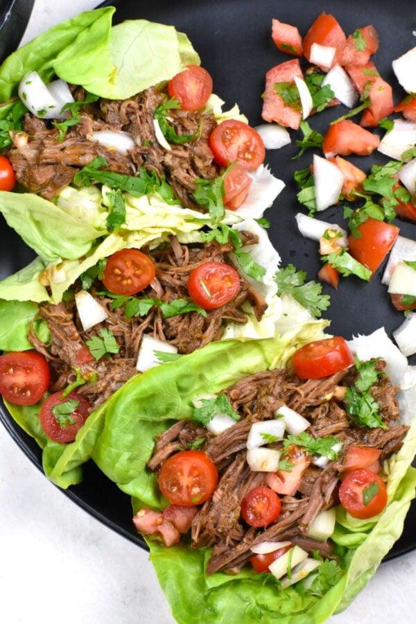 Three barbacoa beef lettuce wraps on a black plate.