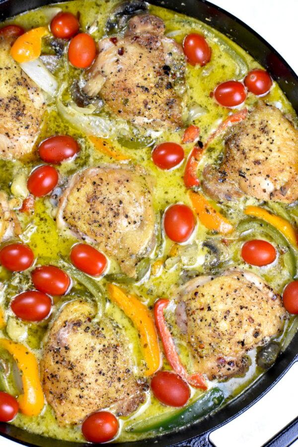 Creamy pesto chicken and veggies in a cast iron skillet.