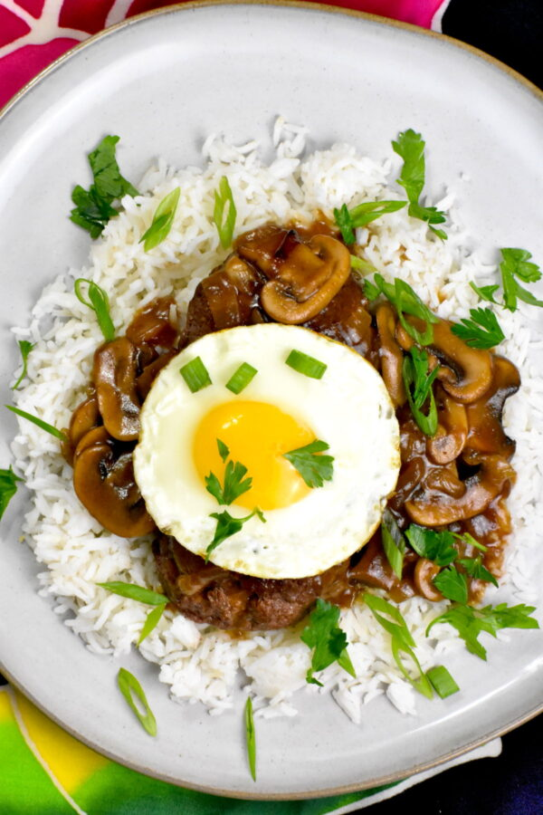 Rice topped with a ground beef patty, mushroom gravy, and a sunny side up egg.