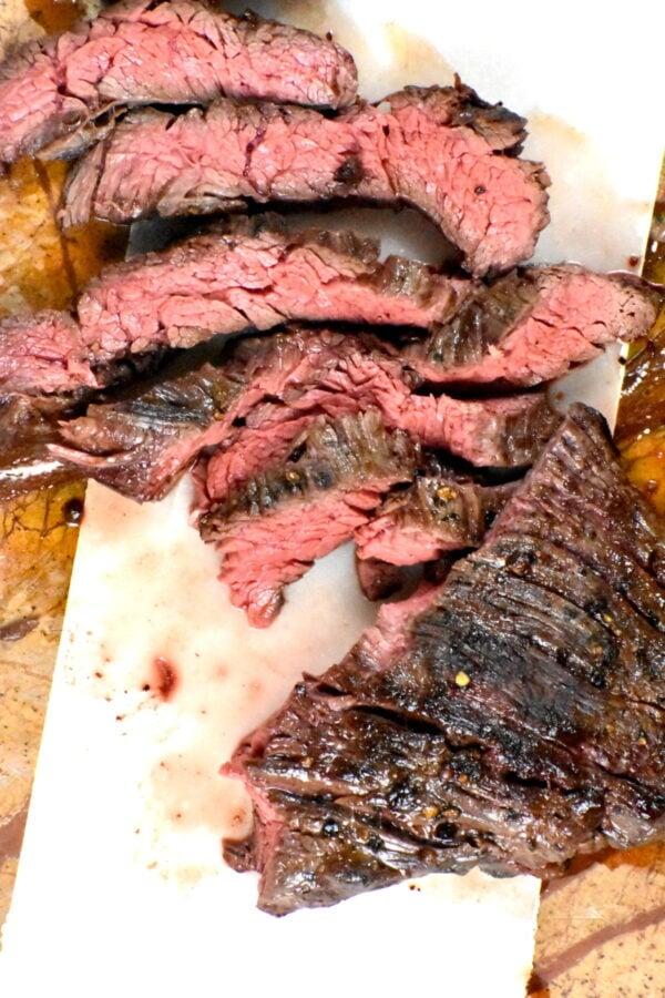 Sliced steak on a cutting board.