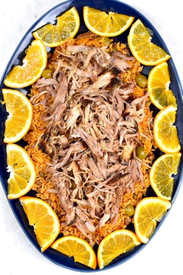 Shredded pork on a platter with rice and orange slices.