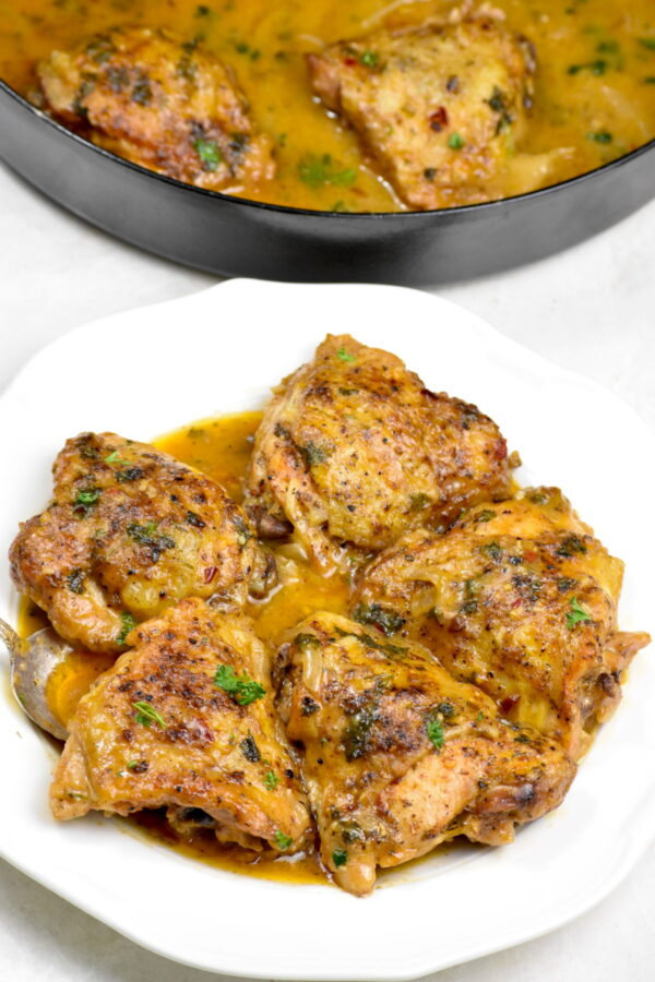 Smothered chicken thighs on a white plate.