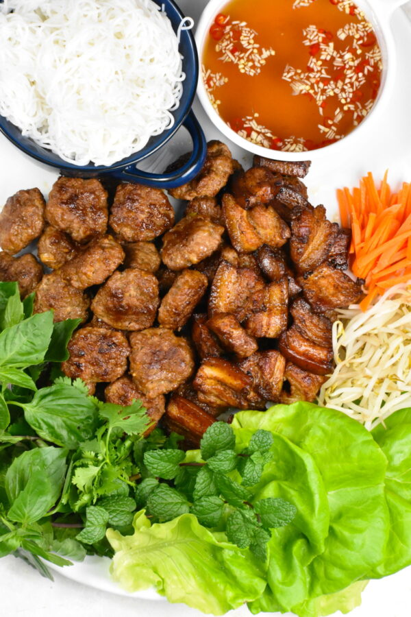 A platter full of meatballs, pork belly, carrots, sprouts, and lettuce.